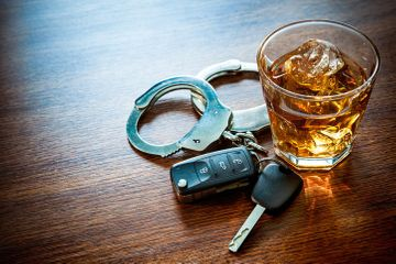 Alcoholic beverage next to car keys and handcuffs