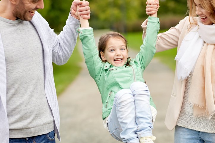 Parents happily swing their daughter between them outside